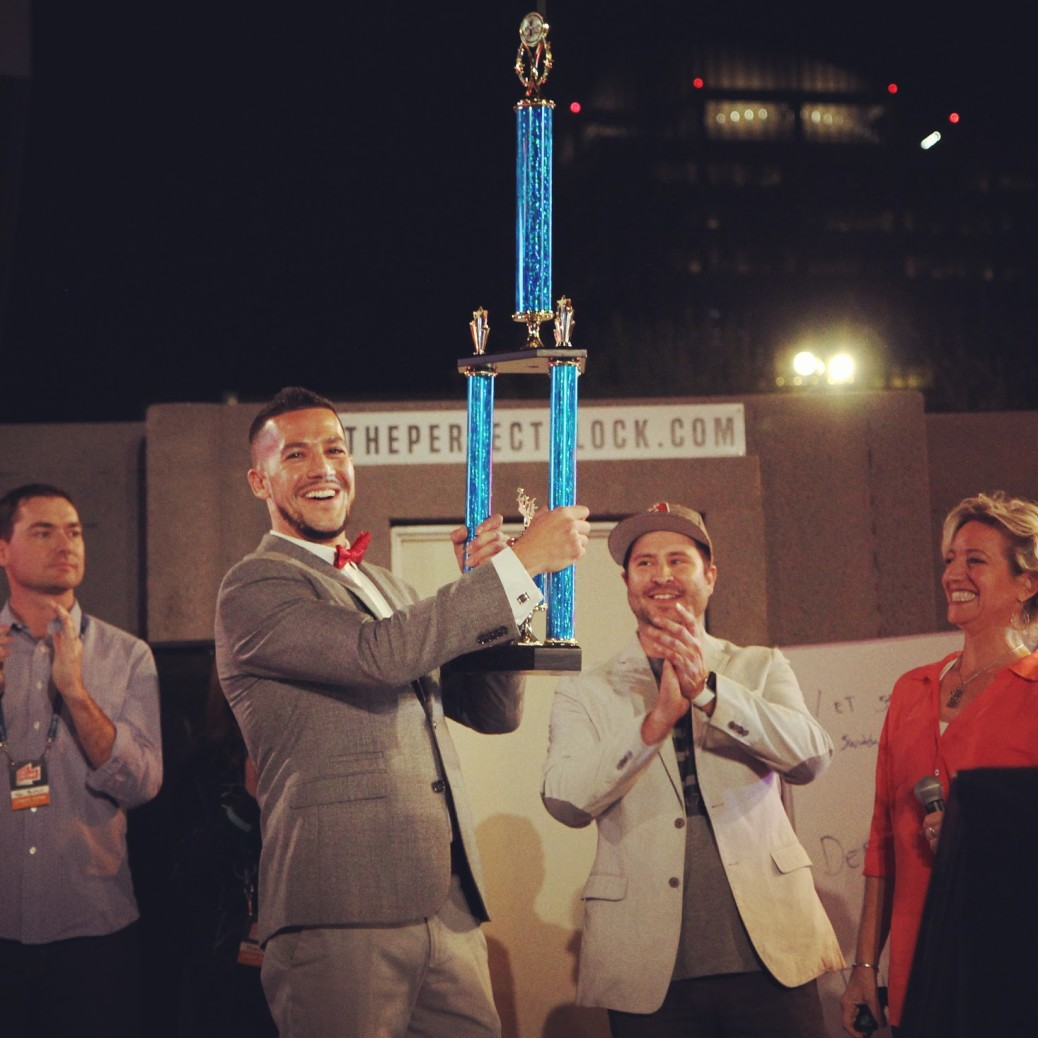 Eric Diaz - latino pitch competition winner holding the trophy